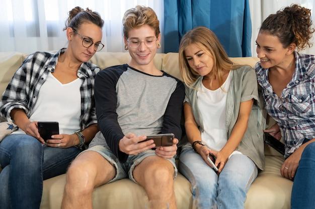 Menino com piercings sorrindo mostrando a tela de um telefone celular ao lado de um grupo de pessoas em um sofá Foto gratuita