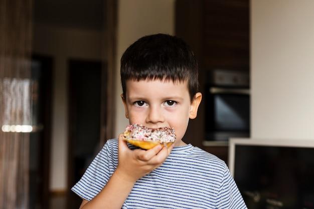 Menino com rosquinha doce em casa Foto gratuita