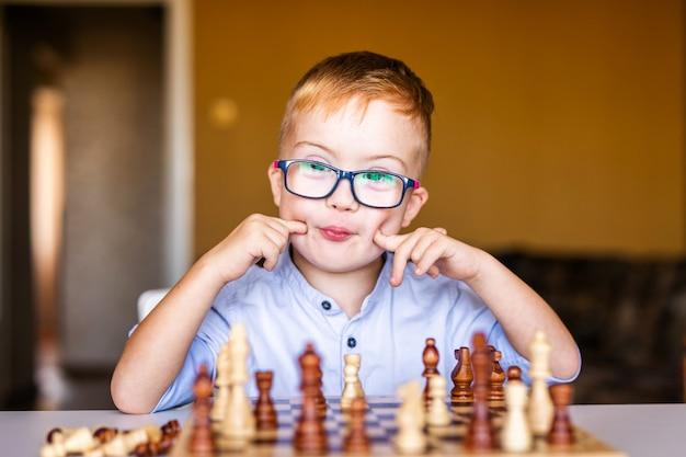 Menino, com, síndrome baixo, com, grande, óculos, xadrez jogando Foto Premium