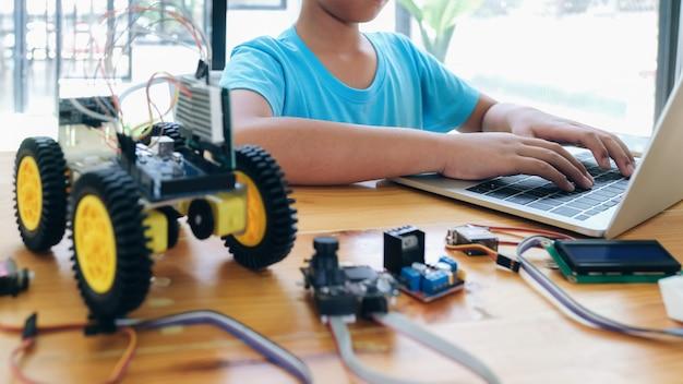 Menino com tablet pc computador programação brinquedos elétricos e construção de robôs. Foto Premium