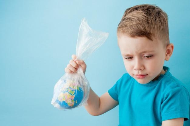 Menino com um globo em um pacote sobre um fundo azul Foto Premium