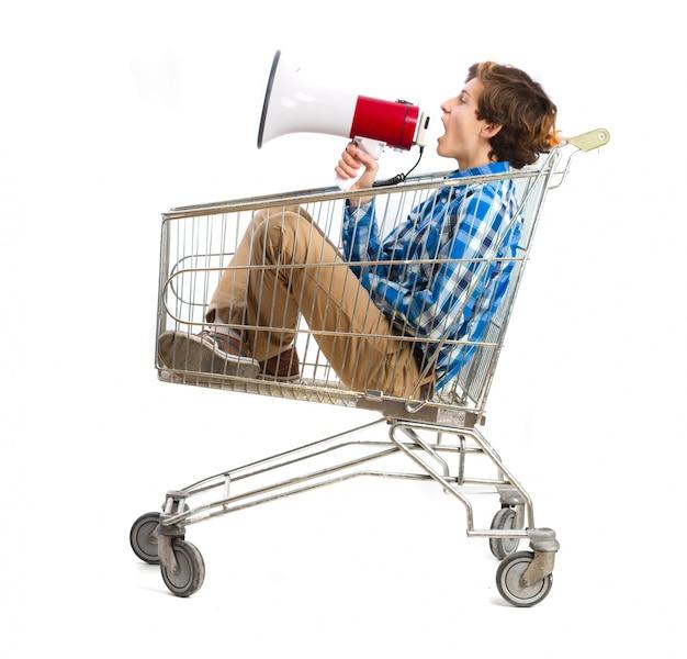 Menino com um megafone em um carrinho de compras Foto gratuita