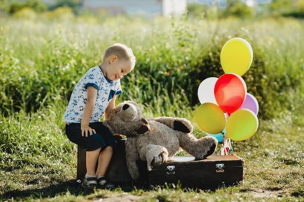 Menino com urso de pelúcia senta-se em uma mala com balões coloridos no campo Foto gratuita