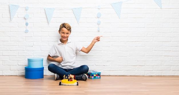 Menino comemorando seu aniversário com um dedo apontando bolo para o lado e apresentando um produto Foto Premium
