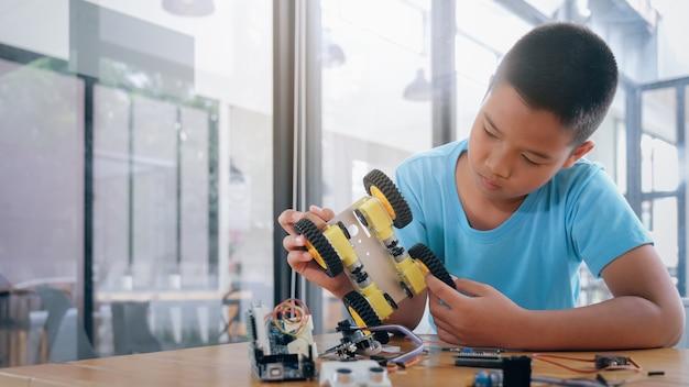 Menino concentrado criando robô no laboratório. Foto Premium
