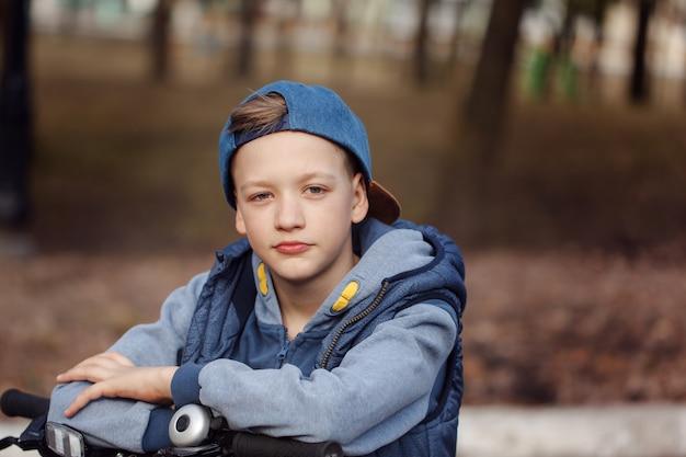 Menino considerável do retrato em uma bicicleta no parque da estrada asfaltada na primavera. Foto Premium