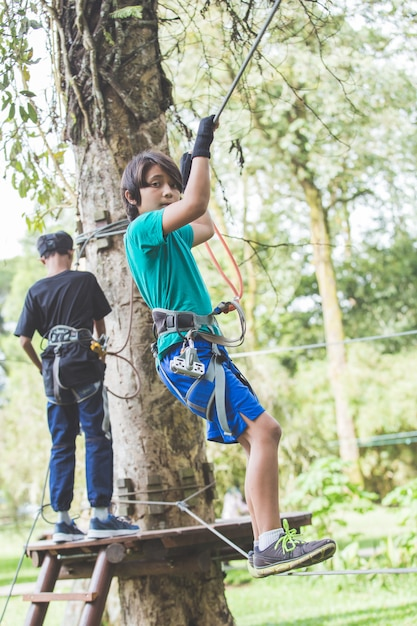 Menino corajoso ativo, desfrutando de escalada de saída no parque de aventura no topo da árvore Foto Premium