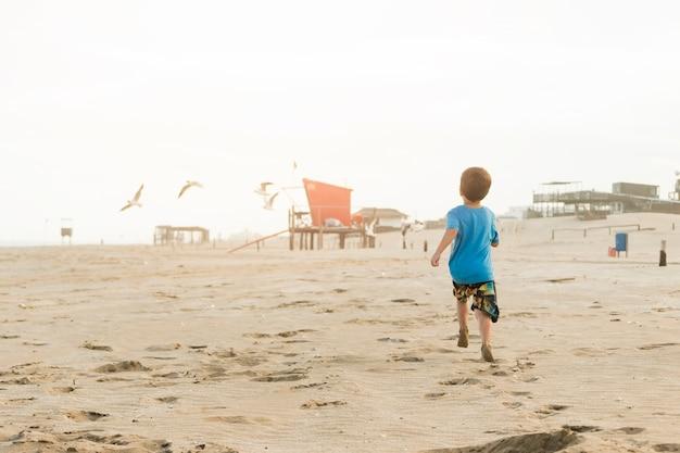 Menino correndo na costa de areia com construções Foto gratuita