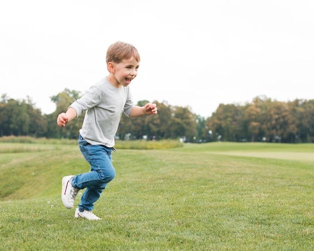 Menino correndo na grama e sendo feliz Foto gratuita