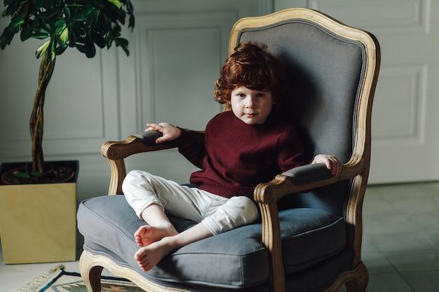 Menino, criança, em, roupa casual, posar, em, a, poltrona Foto Premium