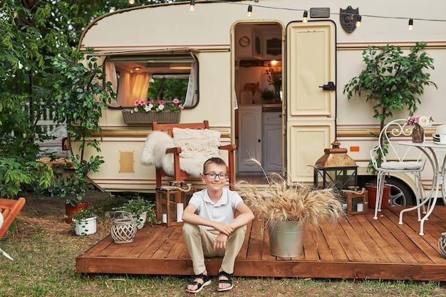 Menino criança perto de uma caravana no verão ao pôr do sol Foto Premium
