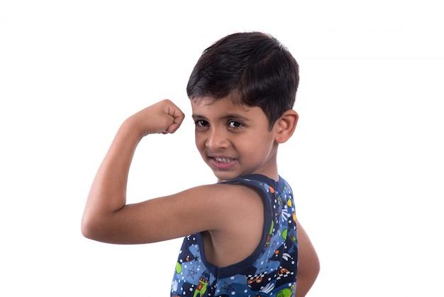 Menino criança sorridente, mostrando sua força de músculos bíceps de mão na parede branca Foto Premium