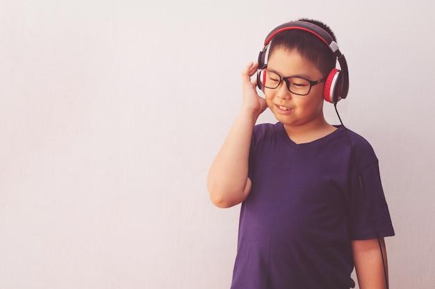 Menino da ásia com fones de ouvido, ouvindo música. Foto Premium