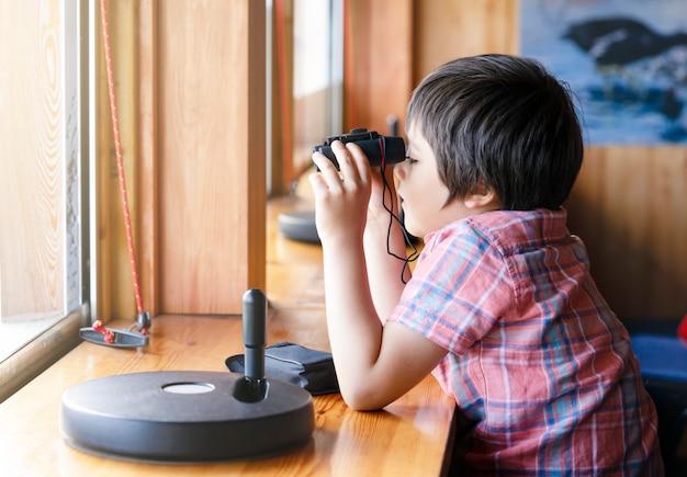 Menino da criança do retrato que olha através dos binóculos no ponto de opinião da estação dos animais. Foto Premium
