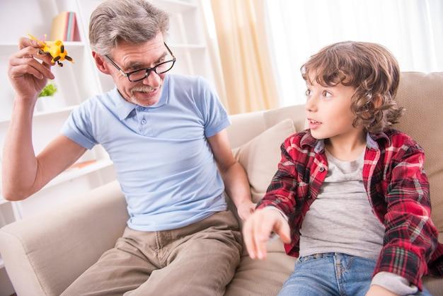 Menino da criança e seu avô estão brincando com um brinquedo de avião. Foto Premium