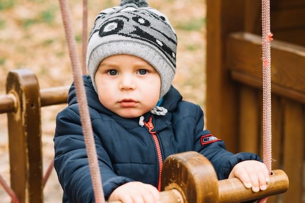 Menino da criança em roupas quentes balançando no parque Foto gratuita