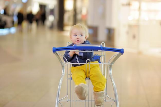 Menino da criança europeia sentado no carrinho de compras Foto Premium