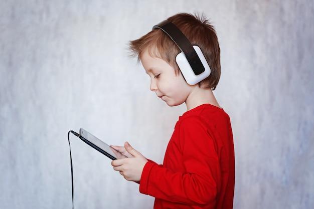 Menino da criança que escuta a música ou que olha o filme com fones de ouvido e que usa a tabuleta digital. Foto Premium