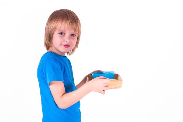 Menino da criança que está com uma bandeja de materiais de montessori para uma lição da vida prática em um fundo branco, Foto Premium