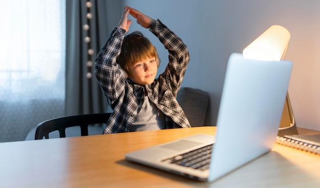 Menino da escola fazendo cursos online e gesticulando Foto Premium