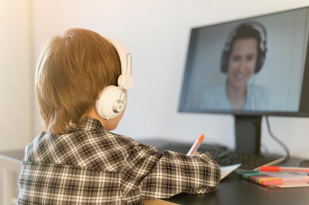 Menino da escola fazendo cursos online e usando fones de ouvido Foto Premium