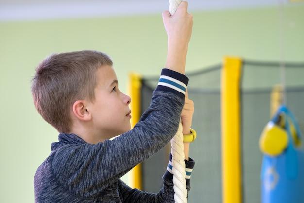 Menino da jovem criança que exercita em uma barra da escada da parede dentro da sala do gym dos esportes em uma escola. Foto Premium