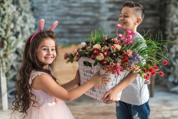 Menino dando saco com flores para menina em orelhas de coelho Foto gratuita