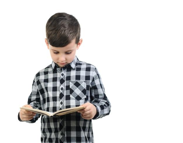 Menino de 6 anos em camisa cinza lê sobre fundo branco isolado, menino olhando para um livro, lendo menino; educação Foto Premium