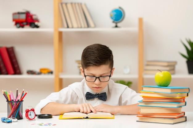 Menino de alto ângulo com óculos de leitura Foto gratuita