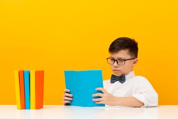 Menino de alto ângulo na leitura do escritório Foto gratuita