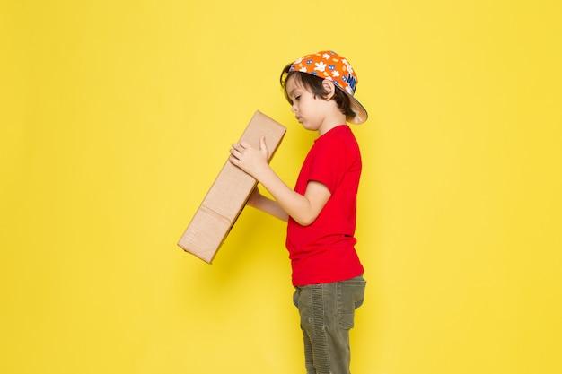 Menino de camiseta vermelha e boné colorido segurando a caixa na parede amarela Foto gratuita