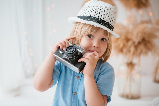 Menino de chapéu de verão segurando uma câmera Foto Premium