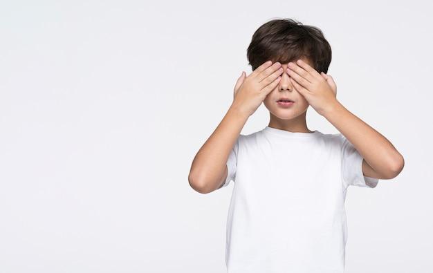 Menino de cópia-espaço brincando de esconde-esconde Foto gratuita