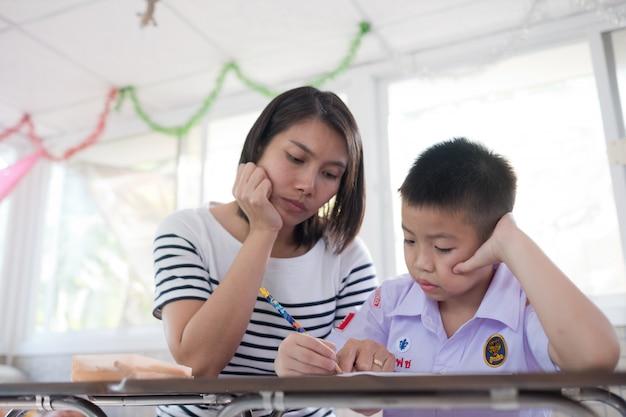 Menino de crianças fazendo lição de casa com a mãe Foto Premium