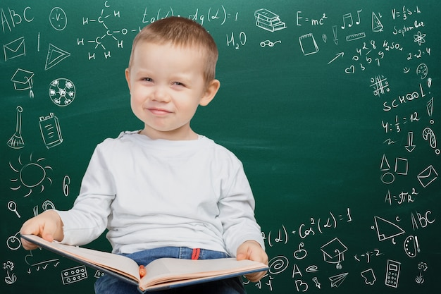 Menino de escola alegre pensativo, volta ao conceito de escola Foto Premium