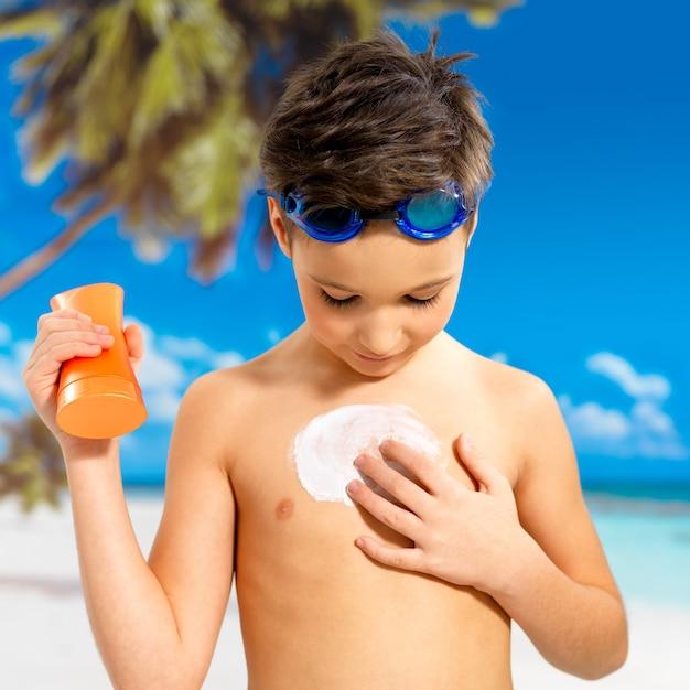 Menino de escola aplicando creme protetor solar no corpo bronzeado. menino segurando o frasco de loção laranja bronzeador. Foto gratuita