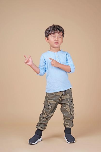 Menino de escola bonito bonito asiático, animado com gestos com os dedos Foto Premium