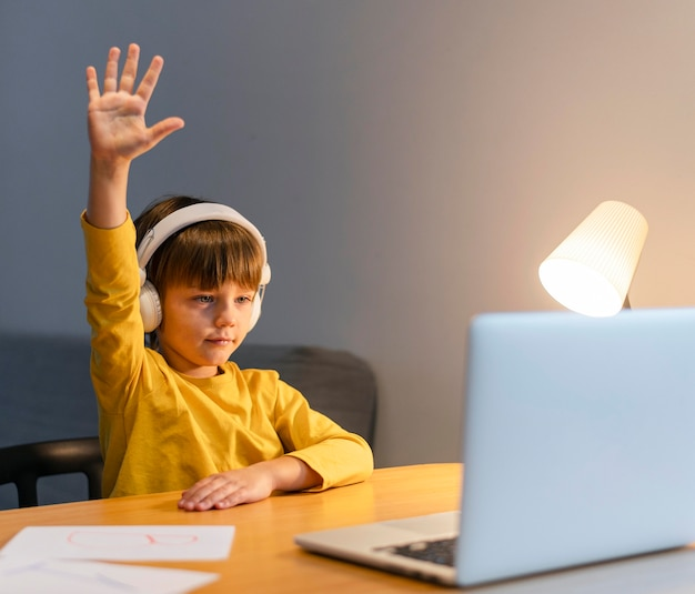Menino de escola com camisa amarela fazendo aulas virtuais e levantando a mão Foto gratuita