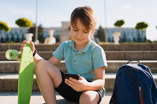 Menino de escola em camisa polo azul, sentado na escada com uma mochila azul e placa verde centavo usando smartphone Foto gratuita