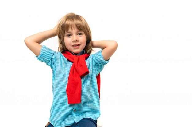 Menino de esportes em t-shirt com capuz em volta do pescoço gesticula isolado em azul Foto Premium