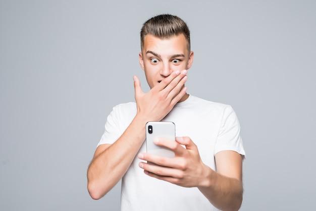Menino de estudante brincando com seu celular isolado no branco Foto gratuita