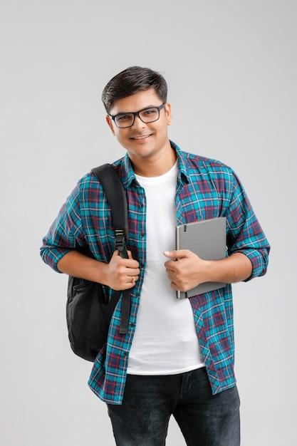 Menino de faculdade indiano segurando o saco e tablet Foto Premium