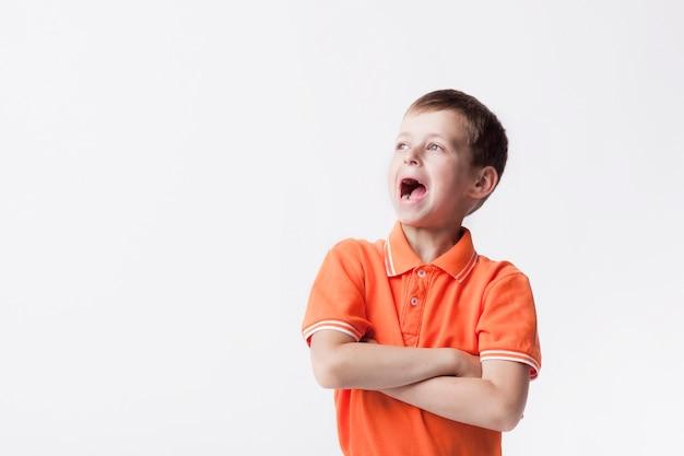 Menino de gritar bonito caucasiano com a boca aberta e braço cruzou em pé sobre fundo branco Foto gratuita