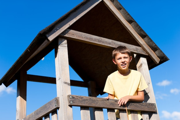 Menino de pé no assento alto de madeira Foto Premium