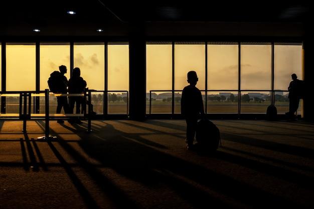 Menino de silhueta no terminal airtport ao nascer do sol Foto Premium