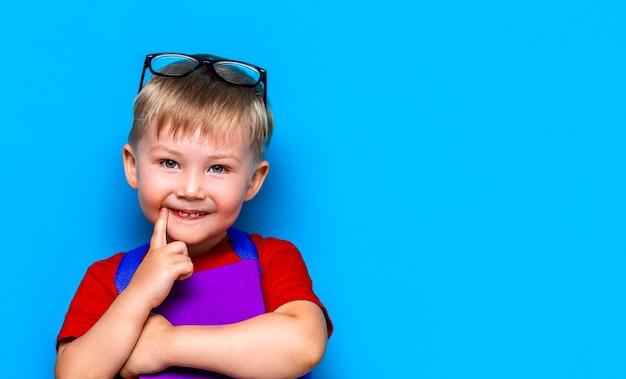Menino de sorriso feliz pequeno com vidros em sua cabeça, livro nas mãos, schoolbag em seus ombros. de volta à escola. pronto para a escola Foto Premium