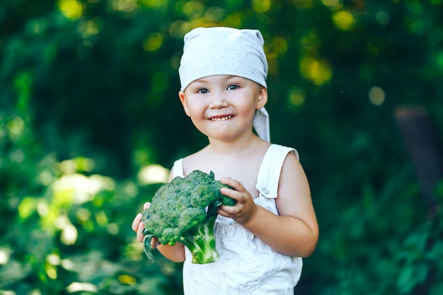 Menino de sorriso feliz pequeno do fazendeiro nos macacões brancos e na faixa cinzenta que guarda brócolis frescos nas mãos. Foto Premium