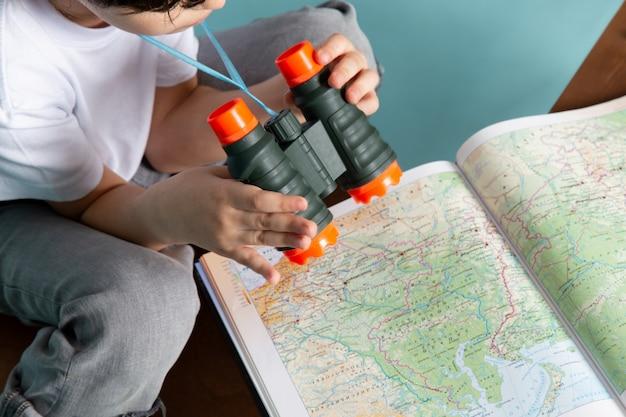 Menino de vista frontal, olhando através do mapa com binóculos Foto gratuita