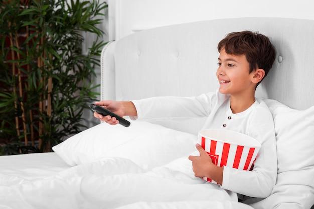 Menino de vista lateral na cama com controle remoto e pipoca Foto gratuita