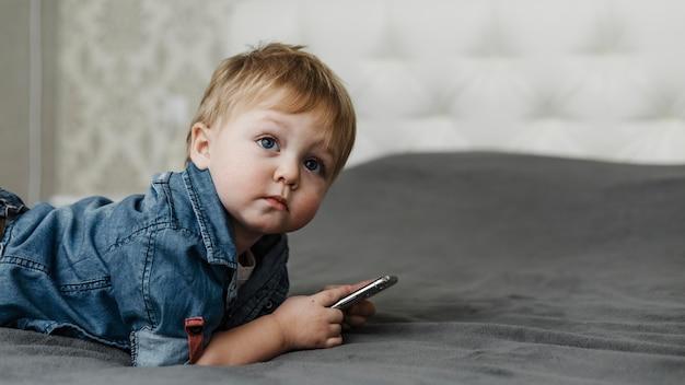 Menino deitado na cama segurando um telefone celular Foto gratuita